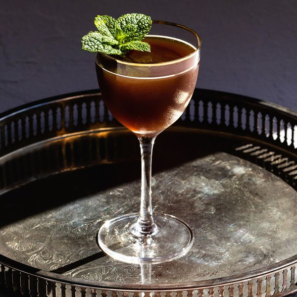 A Nick & Nora glass with a copper rim rests on an elegant bar tray. The glass holds a brown, opaque cocktail.