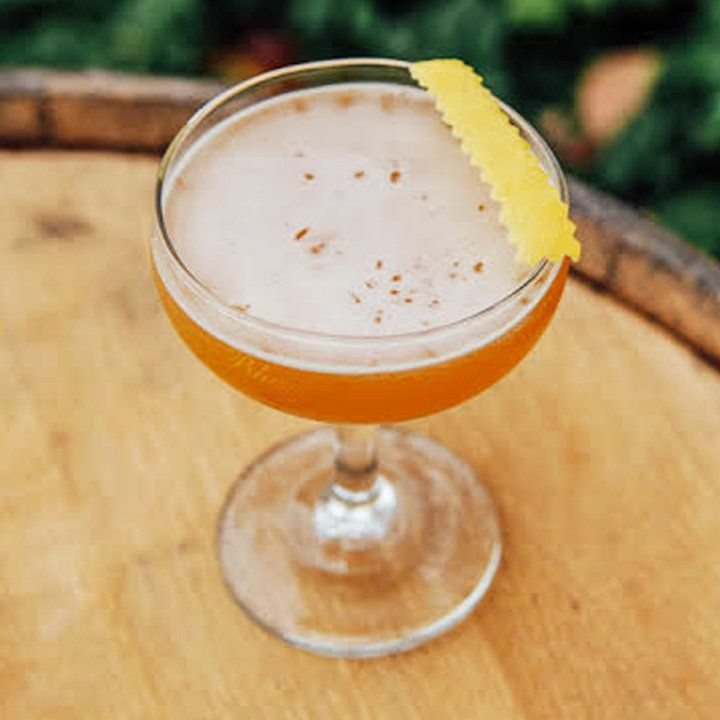 A cocktail coupe sits on a wooden barrel, and is filled with an orange drink. A pinked lemon peel rests on the mouth of the glass.