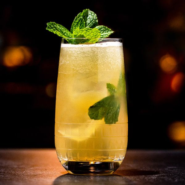 A rounded Collins glass glows with warm light against a dark background. The glass is filled with ice cubes, mint and a light gold sparkling Mojito, and is garnished with a sprig of mint.