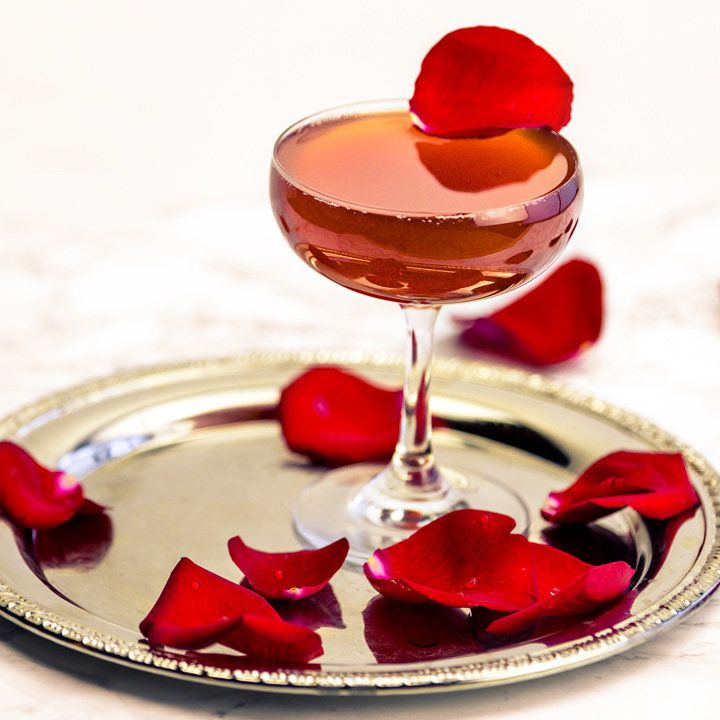 A swooping coupe glass is filled to the brim with a pink, sparkling drink. The glass is topped with a single red rose petal, and many more sit around it base on a golden platter.