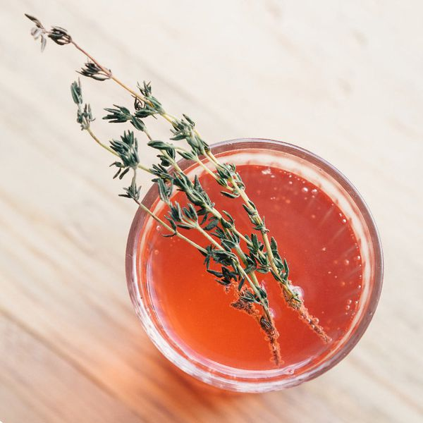 An overhead shot shows a highball glass resting on a pale hardwood surface. The glass is filled with a bubbly red-orange drink and garnished with two sprigs of thyme.