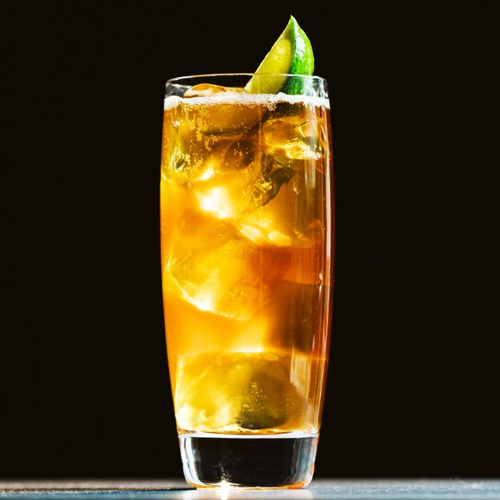 Dark and Stormy cocktail with a lime wedge, served against a black background