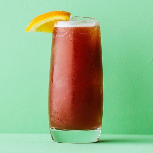 alabama slammer cocktail with orange garnish and green background