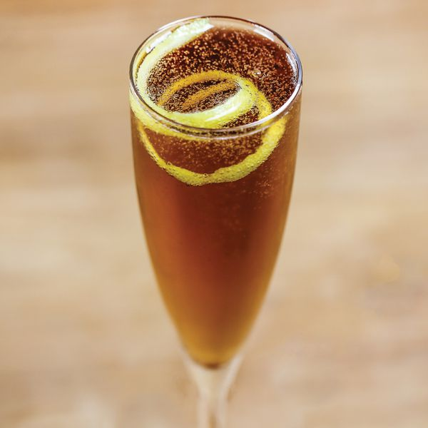 kir royale cocktail in a champagne flute with a lemon twist