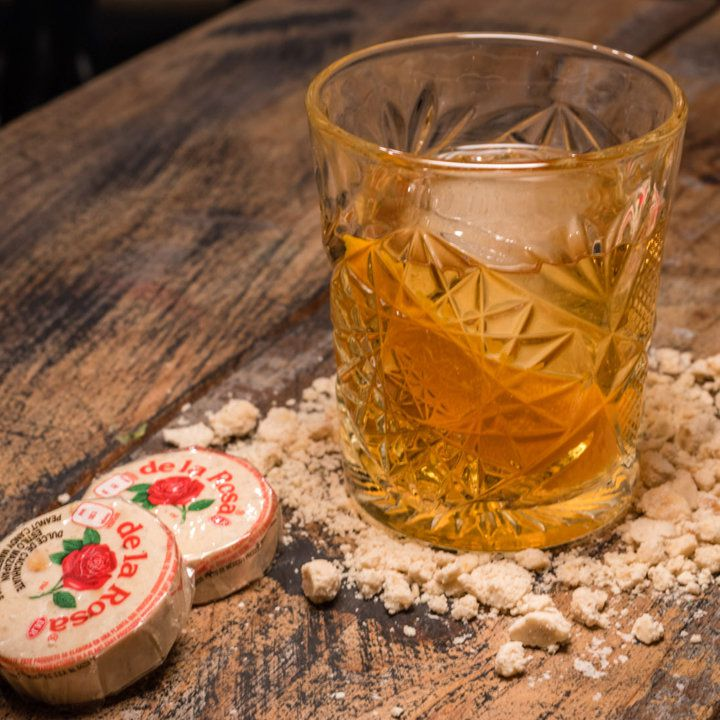A rocks glass with a star insignia etched in the glass sits on a wooden table. It's filled with a large ice cube, a pale gold drink, and an orange peel. Around it is crumbled marzipan and two De La Rosa candies.