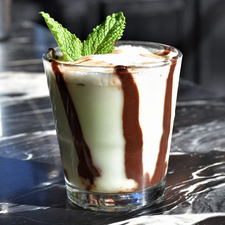 A shot glass sits on a black marble countertop; it is filled with a green, creamy elixir and lines of chocolate streak it like an inverse of the counter top. It is garnished with two small mint leaves.
