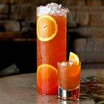 red-orange-colored Boat House Punch served in a cylindrical pitcher garnished with orange wheels and a small punch glass garnished with a half orange wheel