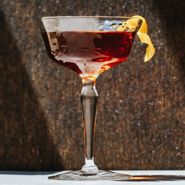 An embellished, angular cocktail coupe holds a crimson drink and a long, curled lemon zest. It's set against a stone wall and rests on a white base.