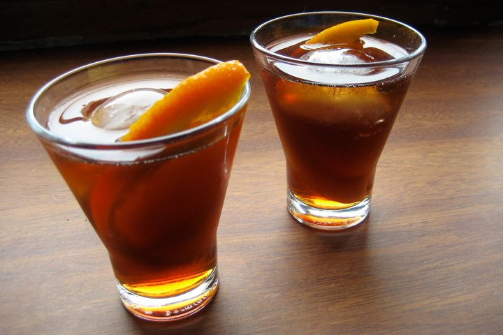 Two glasses of amber-hued homemade vermouth with ice and orange slices