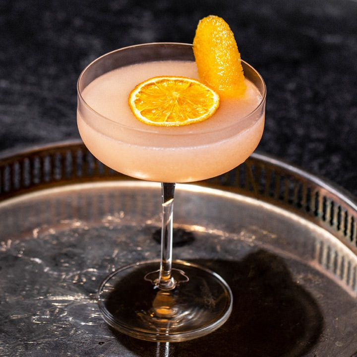 A flat coupe glass is filled with a pink-orange Cosmopolitan variation. A dehydrated orange wheel floats in the center of the drink, while an orange peel pokes up as a garnish. The drink is presented on a silver platter with a tall rim.