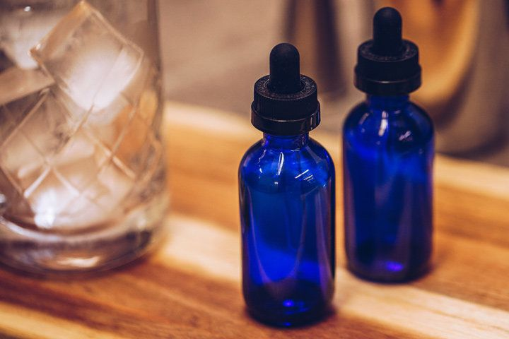 Two small emerald-blue glass bottles with black stoppers sit on a wooden tray. Next to them rests a mixing glass full of ice cubes