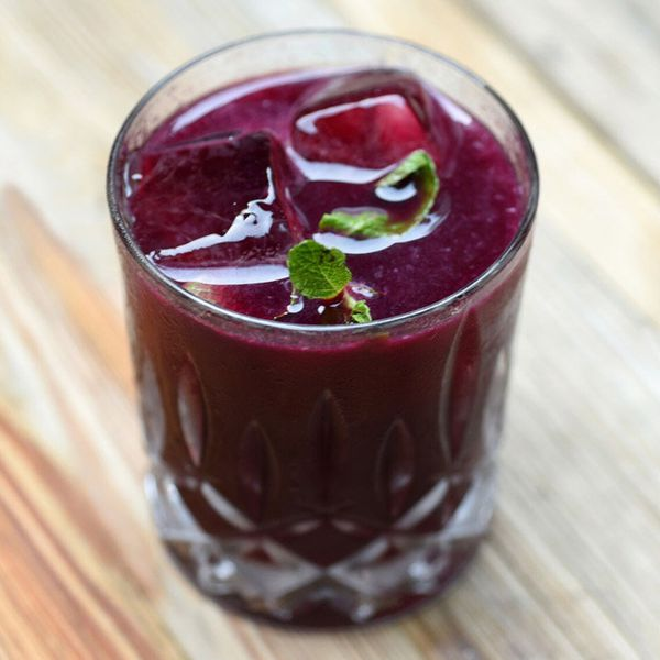 A faceted rocks glass holds a bright purple drink garnished with a few small mint leaves. The glass is resting on a wooden surface.
