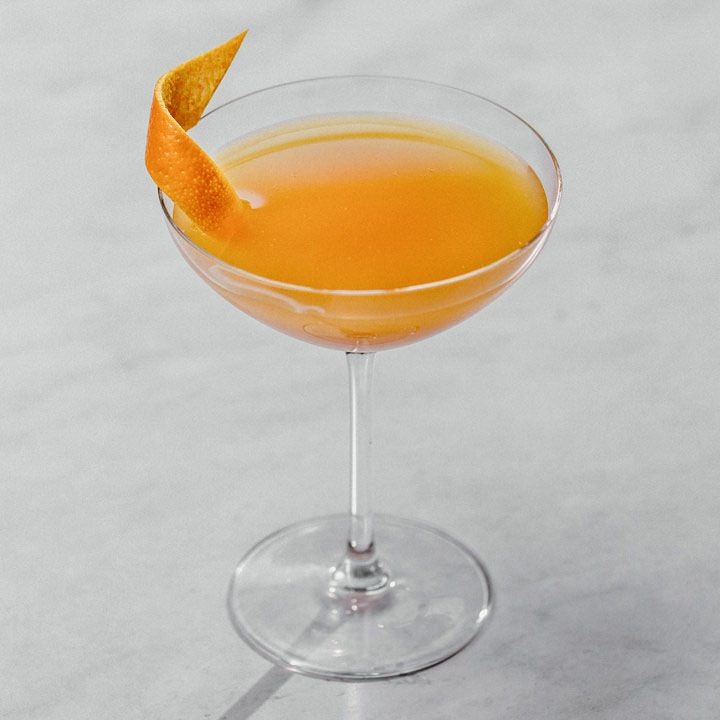 orange-colored Roosevelt cocktail in a cocktail glass, garnished with an orange twist