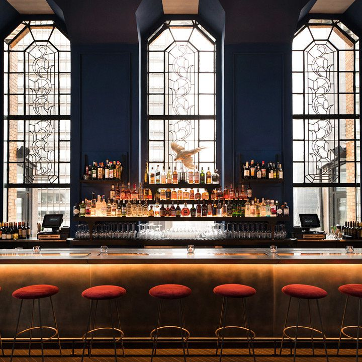 Ophelia interior with view of bar and floor-to-ceiling stained glass windows behind the bar itself