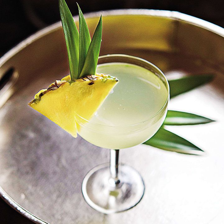 light-yellow Hanalei Sun cocktail in a coupe with a pineapple garnish, served on a round tray