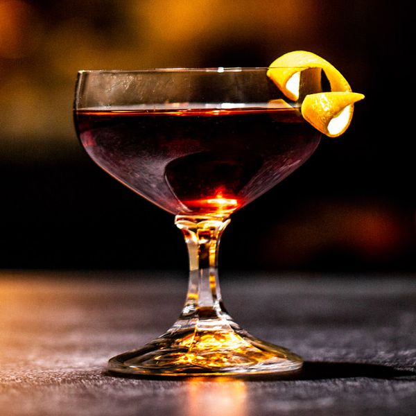 burgundy-colored Princess Mary's Pride cocktail in a short-stemmed cocktail glass, garnished with an orange twist