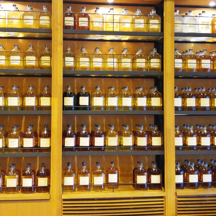 Yamazaki Distillery tasting room. Bottles are right next to each other, packing the shelves of the room