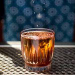 An elegant, faceted Old Fashioned glass sits on a perforated sheet of metal behind a bar. The drink within is red-gold, and a large ice cube is garnished with granulated grasshopper salt. A few flakes of the salt fall from above.