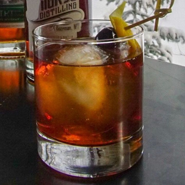 A heavy-bottomed rocks glass is filled with a single large ice cube and a red-orange drink. It's garnished with a cherry and an orange peel. It sits on a dark counter, and a window behind it shows a snowy setting.