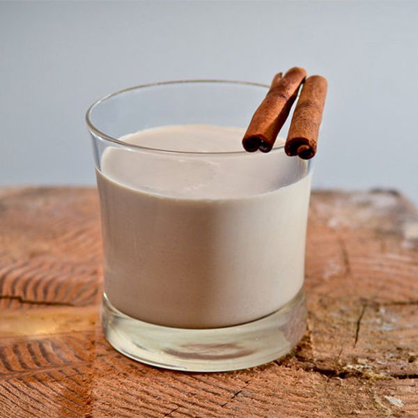 A clear rocks glass filled with creamy Coquito and garnished with two cinnamon sticks
