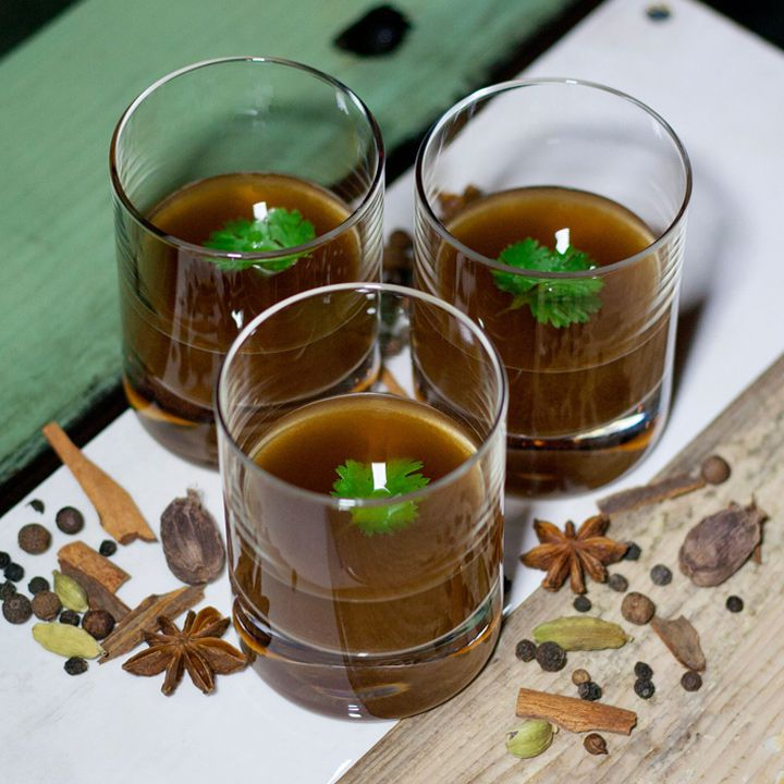 Three short glasses with broad bases hold a strangely dark brown and cloudy drink, the pho-based Pho-King Champ. They are surrounded by dried spices and each garnished with a single cilantro leaf.