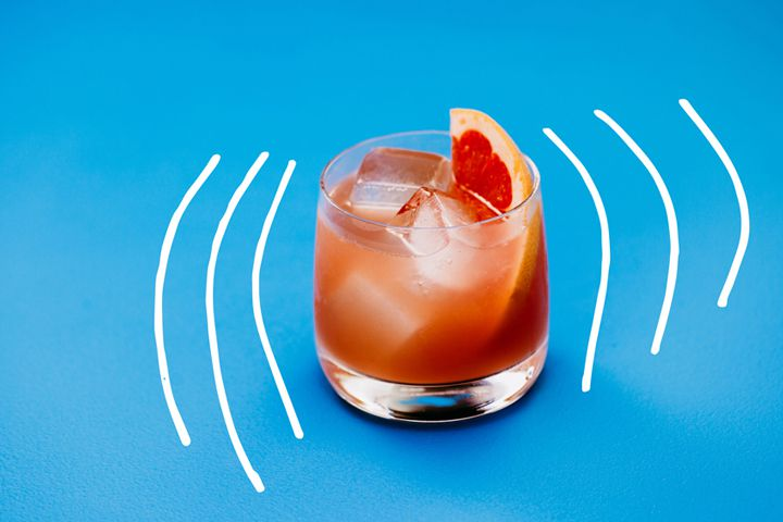 Photo illustration of pink Lounge Chair Afternoon cocktail in rocks glass with grapefruit garnish on blue background with white hand-drawn lines