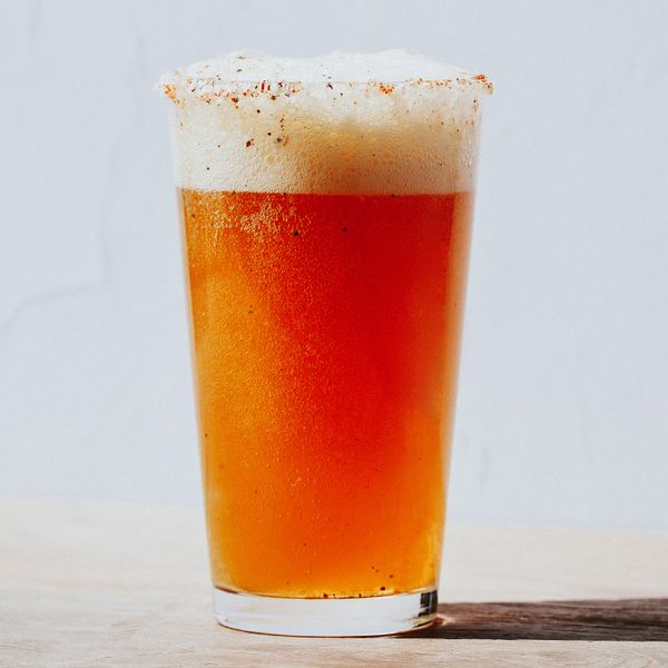 Michelada in a pint glass on a wooden surface
