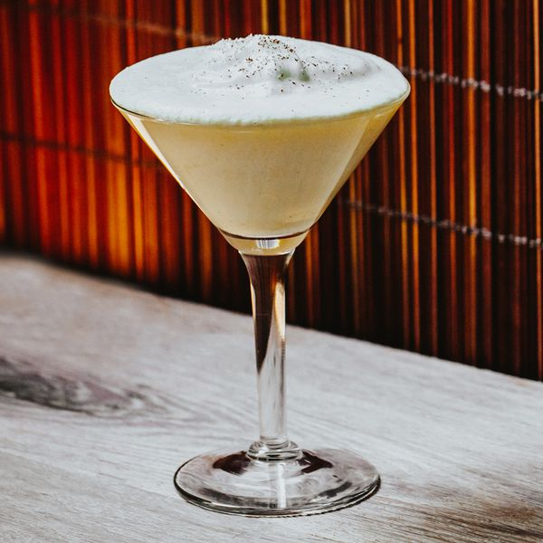 A Martini glass rests on a wooden surface with a slatted wooden wall behind it. The glass is filled with a creamy beige Eggnog with thick white foam.