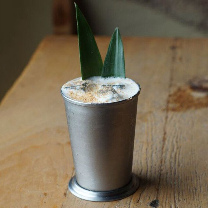 A silver Julep cup rests on a rustic wooden table. The cup is filled with a foamy white drink, dusted with nutmeg and garnished with pineapple fronds.
