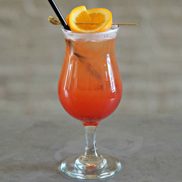 A red-hued Spritz in a hurricane glass, garnished with an orange wheel on a pick