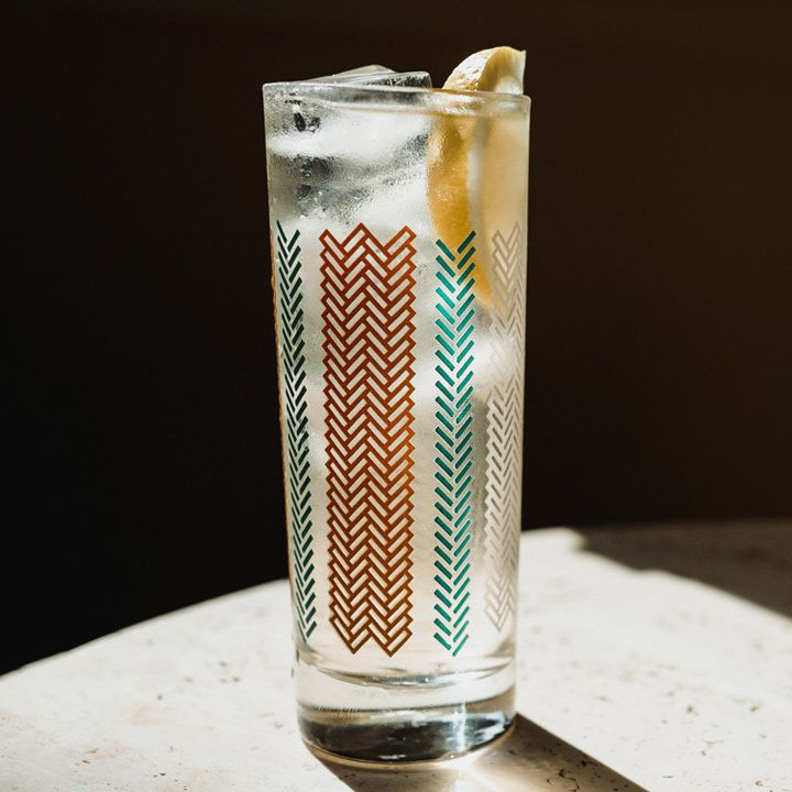 A highball glass sits on a dramatically lit stone surface. It is marked with red and blue chevrons, and is filled with a clear sparkling drink, ice and a lemon wedge.