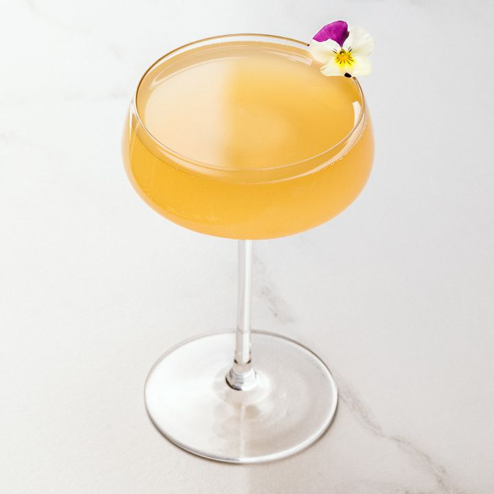 A thin-stemmed, wide-mouthed coupe rests on a marble surface. It holds a vivid orange drink and is garnished with a single pansy.