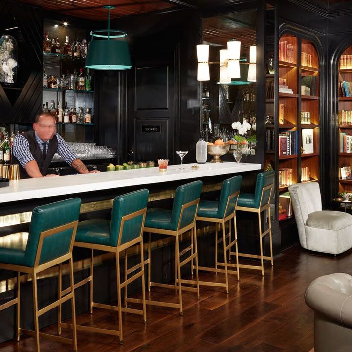 The Spectator Bar interior with teal-backed high stool at the bar and backlit bookshelves near the bar