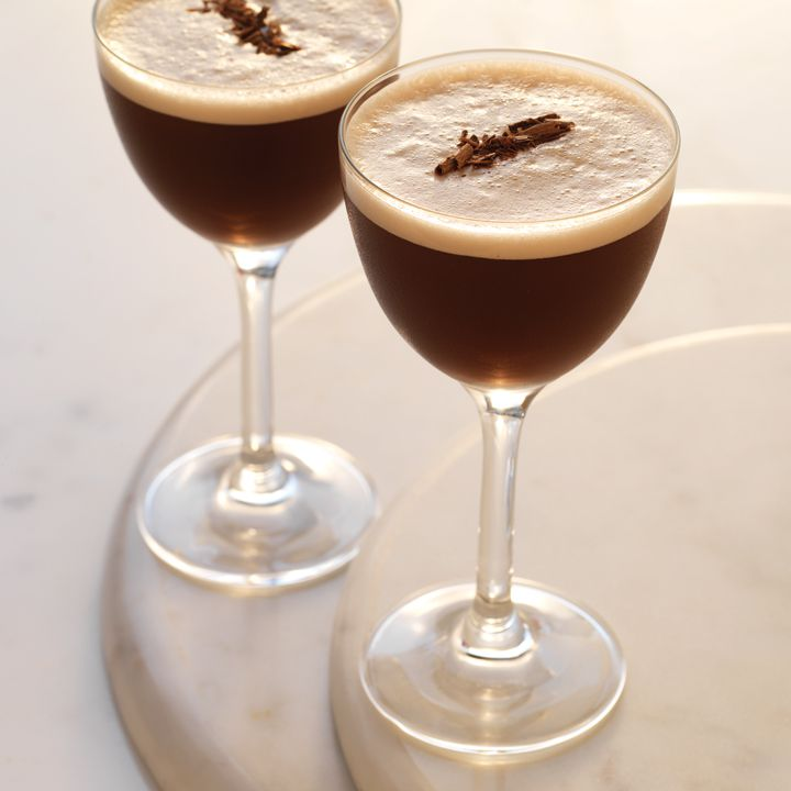 Two Nick & Nora glasses rest on a white surfaced, lit with a soft light. The glasses are both filled with a dark brown drink topped with white foam and chocolate shavings.