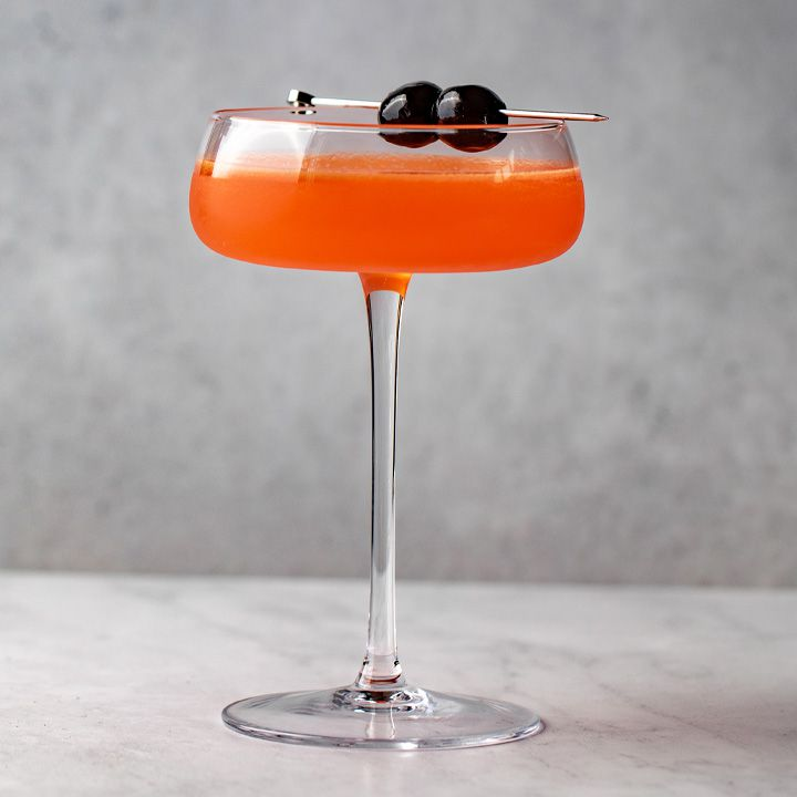 A long-stemmed coupe with a short flat bowl holds a bright orange cocktail. The drink is garnished with two dark cherries on a metal pick. The background and floor are both gray marble.