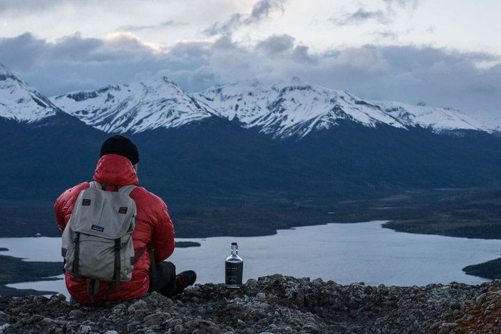 A man in a red jacket sitting next to a bottle of Trakal while looking out over a river and snow-capped mountains