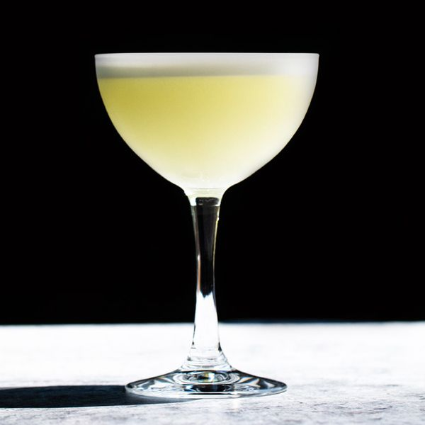 A brightly lit cocktail coupe holds a vidid yellow cocktail with a white foamy head. The glass stands on a white stone surface, with a jet black background.