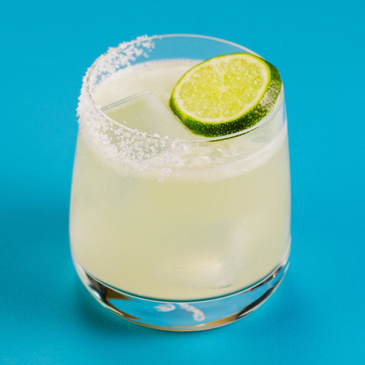 A rocks glass that tapers towards the top holds a Margarita. Half its rim is coated with salt and the other side has a lime wheel garnish. The background is solid blue.