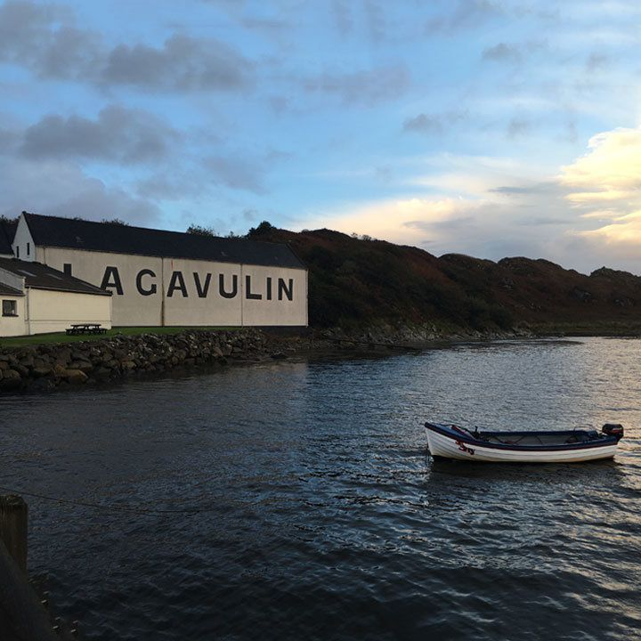 """Lagavulin distillery in Islay, Scotland. The word """"Lagavulin"""" is written in huge block letters across the side of a buildling and a wee canoe is in the open water in front of the buildilng"""