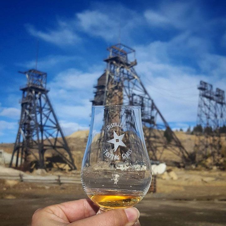 Headframe Spirits, Montana with oil rigs in the background