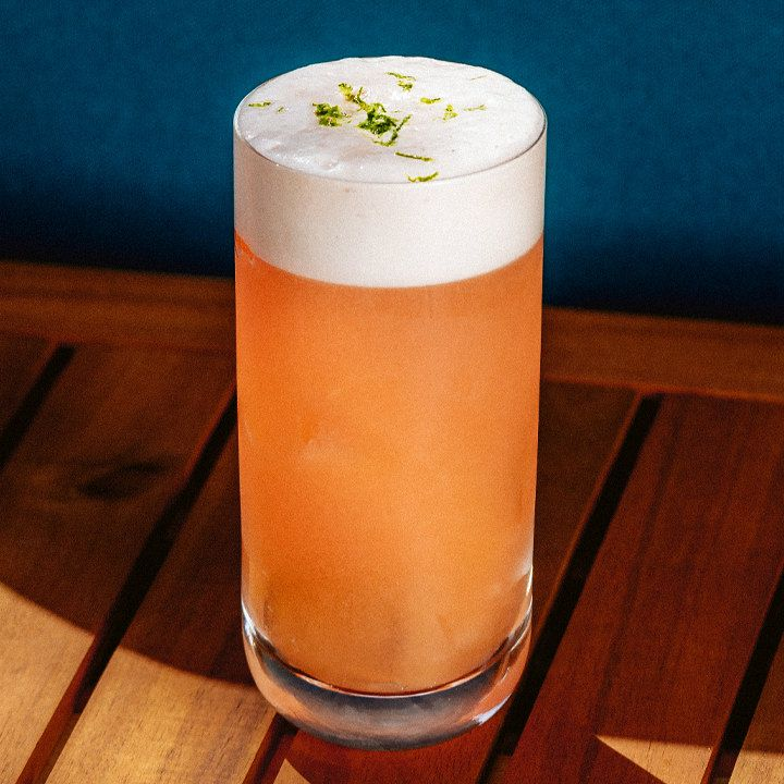A Collins glass sits on a slatted wooden table against a blue wall. The drink within is opaque orange and topped with a thick head of foam, which is garnished with lime zest.