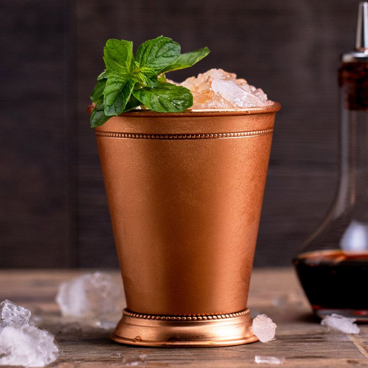 A Mint Julep in a classic metal cup and a dasher bottle surrounded by crushed ice.