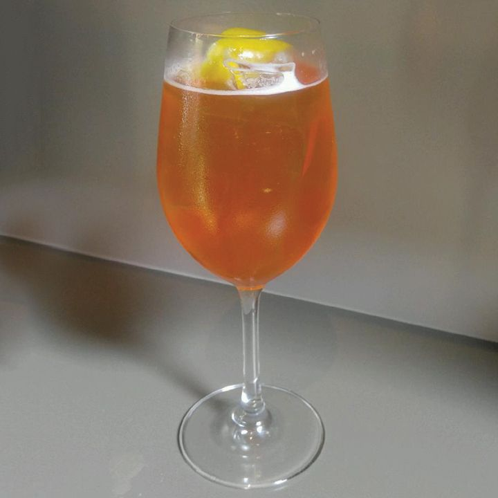 A wine glass stands on a neutral gray background, and is filled with a red-orange bubbly drink. A few ice cubes float in the glass, and it's garnished with a lemon peel.