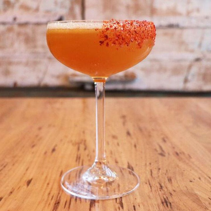 A tall stemmed coupe glass rests on a wooden floor with a metal door in the background. The glass is filled with an orange cocktail and dusted with aleppo powder.