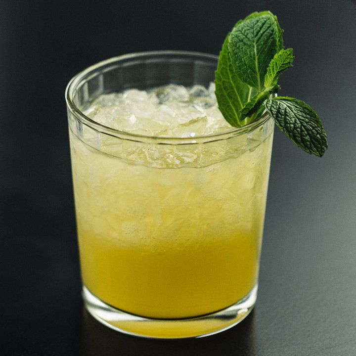 A yellow-hued Mai Tai on crushed ice garnished with a mint sprig