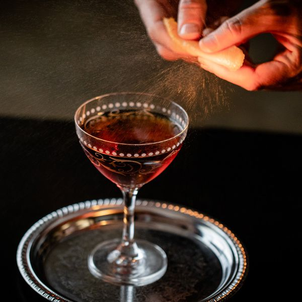Hands express orange peel oils over the top of the Longshoreman cocktail