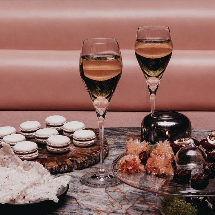 Two Champagne flutes with macarons at Botanist bar at Fairmont Pacific Rim