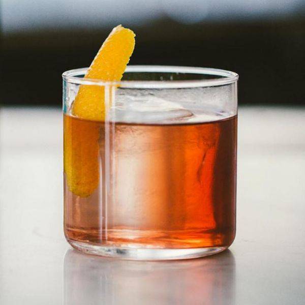 A short rocks glass with thin walls holds a vivid red-orange cocktail over a large, clear ice cube. A thin slice of orange peel is the only garnish, and the background of the photo is indistinct and hazy.