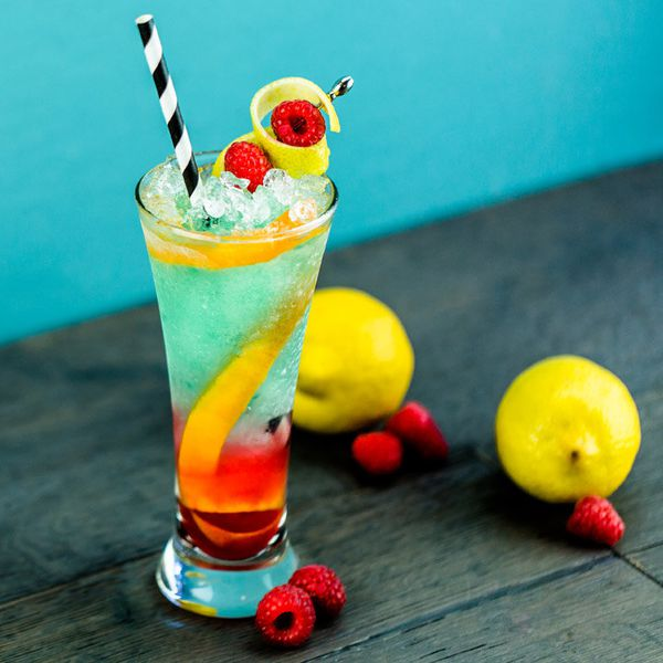 Teal-quila Sunrise cocktail layered in a highball glass with red on bottom and blue on top, garnished with two raspberries wrapped in a lemon peel