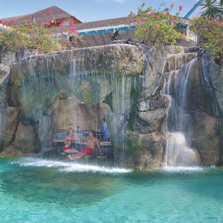 Crystal Cove swim-up bar in Barbados. Two patrons are sitting on a barstool near a bar which is tucked under a rock outcropping. A waterfall pours over the area in front of the guests